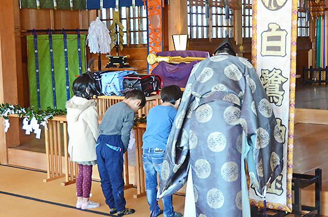 白鷺神社にて 玉串を捧げて、ね宜さんと一緒に二礼二拍手一礼している様子