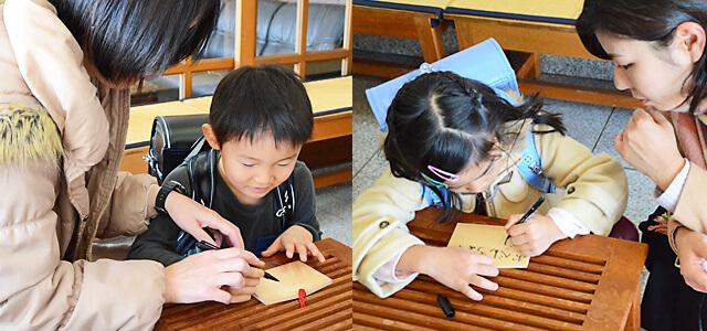 白鷺神社にてランドセル祈願用の絵馬に書き込むお子さんとママさん